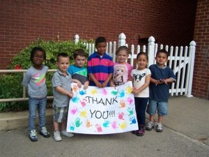Neighborhood Center children holding up a thank you sign